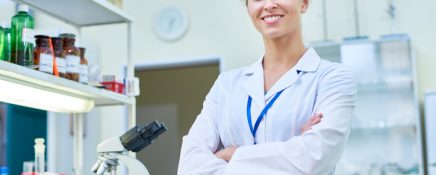 Portrait of young female scientist smiling cheerfully and looking at camera while posing in modern laboratory with arms crossed, copy space